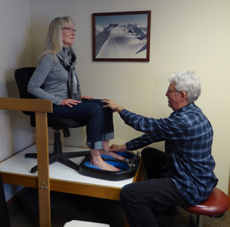 Bob Egeland of Boulder Orthotics, fitting client with custom orthotic
